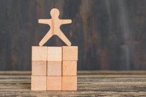 Business success concept with human model on wooden cubes on wooden background side view.